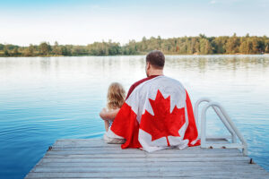 father and child on dock draped with Canadian flag